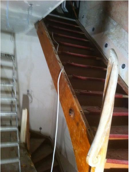 Holztreppe mit augekeptem Teppich vor der Renovierung